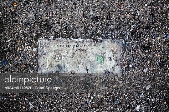 Still life of deteriorating one dollar bill on wet pavement - p924m911082f by Chad Springer