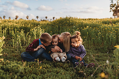 Four siblings smiling at each other in field of flowers with blue sky - p1166m2124403 by Cavan Images