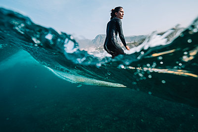 Split image of female surfer surfing a small wave - p1166m2193899 by Cavan Images