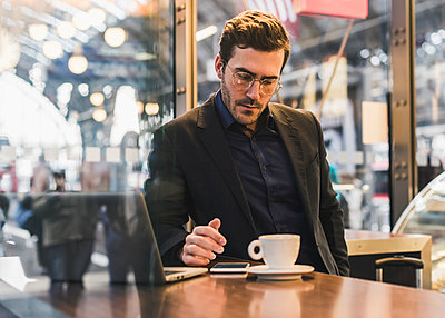 Young businessman in a cafe at train station with cup of coffee, laptop and cell phone - p300m1563365 by Uwe Umstätter