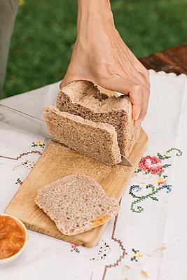 Female hand cutting bread on cutting board in garden - p300m2220516 by Alberto Bogo