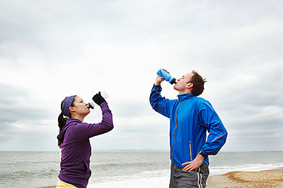 Couple drinking after exercise on beach - p42913709f by Moof