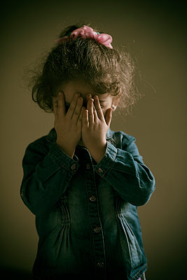 Sad little girl hiding face with hands  - p794m2031107 by Mohamad Itani