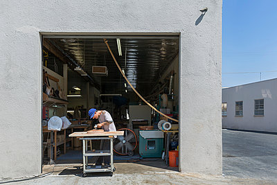 Guitar maker manufacturing guitar outside workshop - p924m1206511 by Ian Spanier