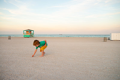 Toddler picking seashells on beach, Miami beach front, Florida, USA - p924m2164686 by Vanessa Lenz