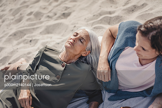Mother and daughter relaxing on the beach - p300m2140144 by Joseffson