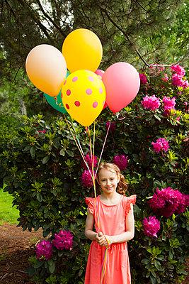 mit Luftballons vor Bougainvillea-Strauch posieren - p045m1461160 von Jasmin Sander