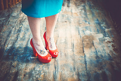 Women in red court shoes - p1150m1112924 by Elise Ortiou Campion