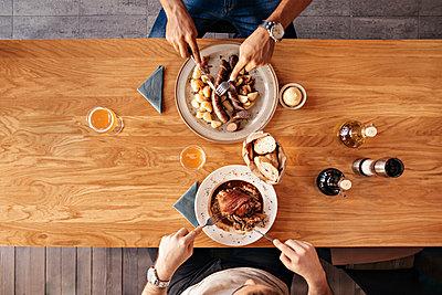 Two men in restaurant having lunch - p300m1101186f by Zeljko Dangubic