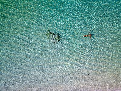 Indonesia, Bali, Melasti, Aerial view of Karma Kandara beach, man swimming - p300m2042556 by Konstantin Trubavin