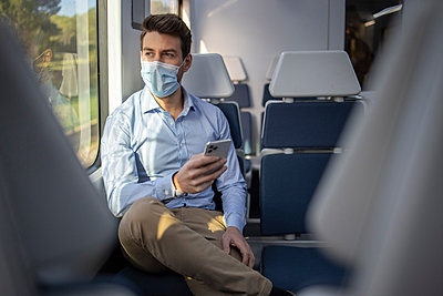 Businessman wearing face mask looking away while using mobile phone sitting in train - p300m2242877 by Ignacio Ferrándiz Roig