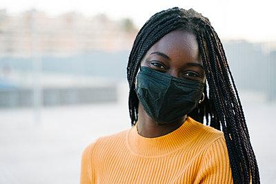 Teenage girl wearing protective face mask outdoors - p300m2243872 by Manu Padilla Photo