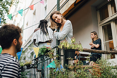 Smiling young woman looking at male friend while standing in balcony during garden party - p426m2046231 by Maskot