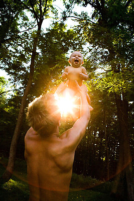 Father lifting baby girl in forest - p9241505 by Bill Miles