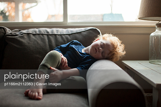Young boy sleeping in funny position on couch at home - p1166m2112383 by Cavan Images