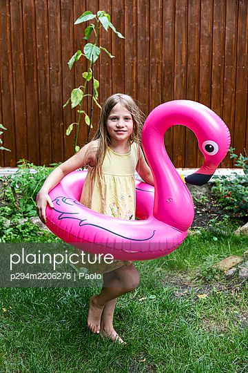 Girl playing with Flamingo swimming ring in the garden - p294m2206278 by Paolo