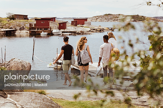 Rear view of friends looking at sea during summer vacation - p426m2238150 by Maskot