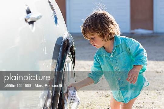Caucasian boy washing car