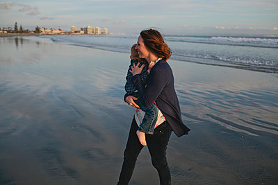 Side view of woman carrying boy while walking at beach - p1166m1210258 by Cavan Images