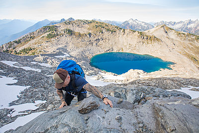 A mountaineer ascends a rocky ridge on Douglas Peak, British Columbia. - p1166m2095142 by Cavan Images