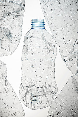 Used water bottles and white background - p1166m2106095 by Cavan Images