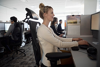 Woman working in cubicle at call center - p1192m2040653 by Hero Images