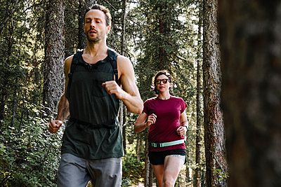 Couple jogging in woods - p1192m2129213 by Hero Images