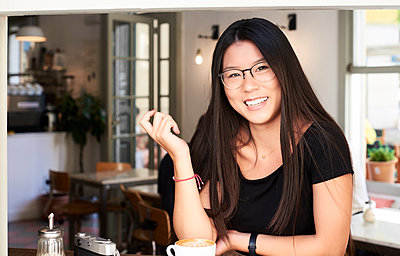 Asian young woman smiling at camera in a coffee shop - p300m1535110 by Ivan Gener Garcia