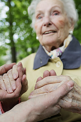 Germany, North Rhine Westphalia, Cologne, Senior woman holding hands of mature woman, close up - p300m2213770 by Jan Tepass