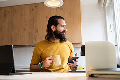 Man with long hair looking away holding smart phone and mug at home - p300m2282056 by Jose Carlos Ichiro