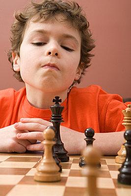 Boy playing chess - p4342509f by Marv Johnson