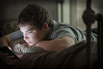 Caucasian boy laying on bed using cell phone - p555m1305209 by Terry Vine