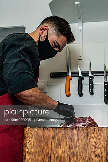 Butcher with mask cutting raw meat in the wood - p1166m2202051 by Cavan Images