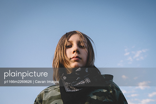 Boy in Camouflage Hoodie and Bandana Against the Open Blue Sky - p1166m2269626 by Cavan Images