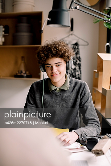 Portrait of smiling curly hair boy wearing headphones sitting at desk - p426m2279718 by Maskot