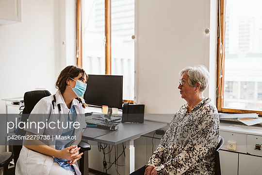 Female doctor consulting senior patient during COVID-19 - p426m2279738 by Maskot