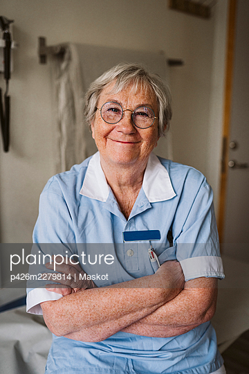 Portrait of smiling senior female doctor standing with arms crossed - p426m2279814 by Maskot