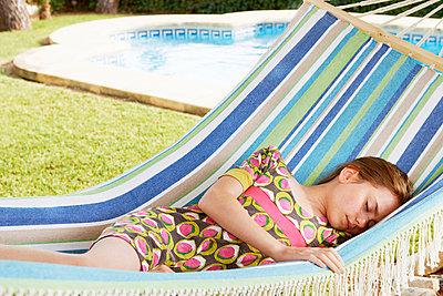 Girl sleeping in hammock - p42912302f by Adie Bush