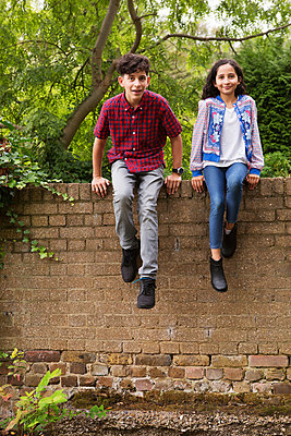 Portrait of brother and sister sitting on wall - p429m1187912 by Nancy Honey