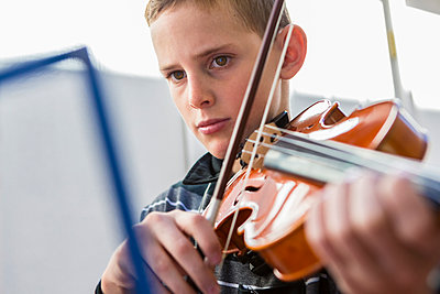 Close up of Caucasian boy playing violin - p555m1410223 by Marc Romanelli