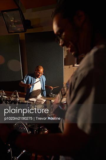 Musicians practicing in recording studio - p1023m2190275 by Trevor Adeline