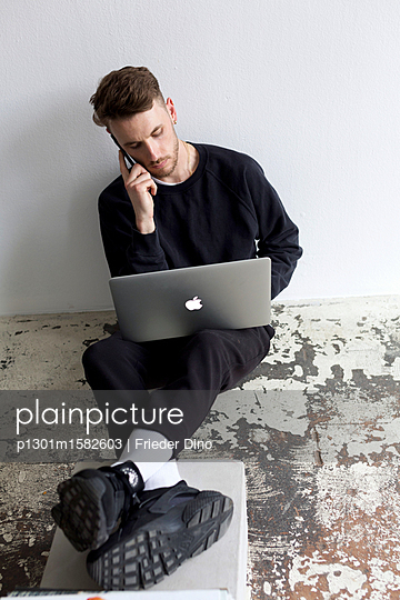 Junger Mann mit Laptop Computer sitzt auf dem Fußboden - p1301m1582603 von Delia Baum