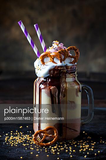 Glass of vanilla milkshake with cacao, chocolate sauce, whipped cream and topping - p300m1587463 von Dieter Heinemann