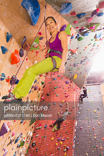 Smiling climber scaling rock wall - p555m1312140 by Don Mason