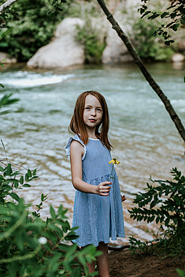 Vertical portrait of a young girl holding a flower next to a river - p1166m2207961 by Cavan Images