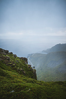 Norway, Lofoten Islands, Reine, Man looking at view fromÊReinebringenÊmountain during rain - p1427m2174065 by Oleksii Karamanov