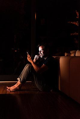 Man sitting on the floor at home looking at smartphone - p300m1587902 von Uwe Umstätter