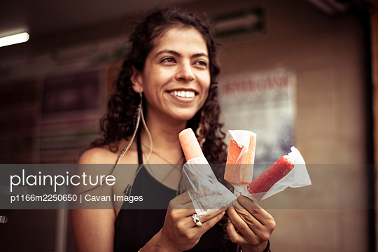 Attractive smiling young alternative Mexican woman with ice creams - p1166m2250650 by Cavan Images