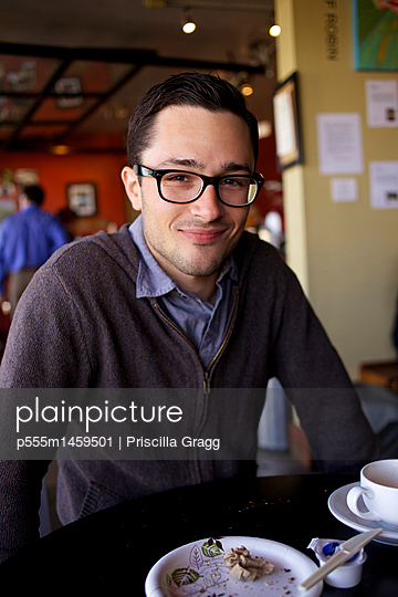 Man smiling at table in cafe - p555m1459501 by Priscilla Gragg