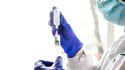 Midsection Of Female Nurse Holding Syringe Against White Background - p1166m2190771 by Cavan Images